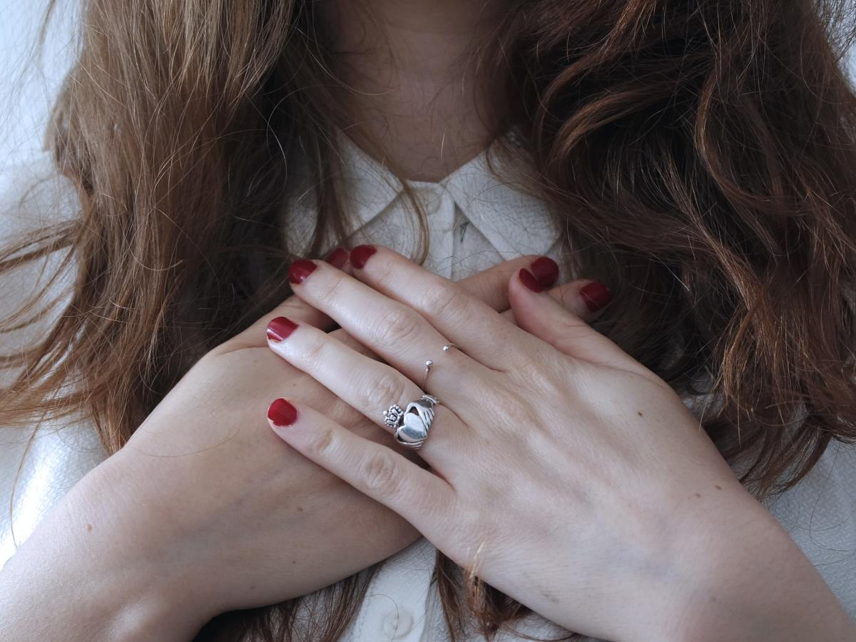 woman with red nails wearing claddagh ring