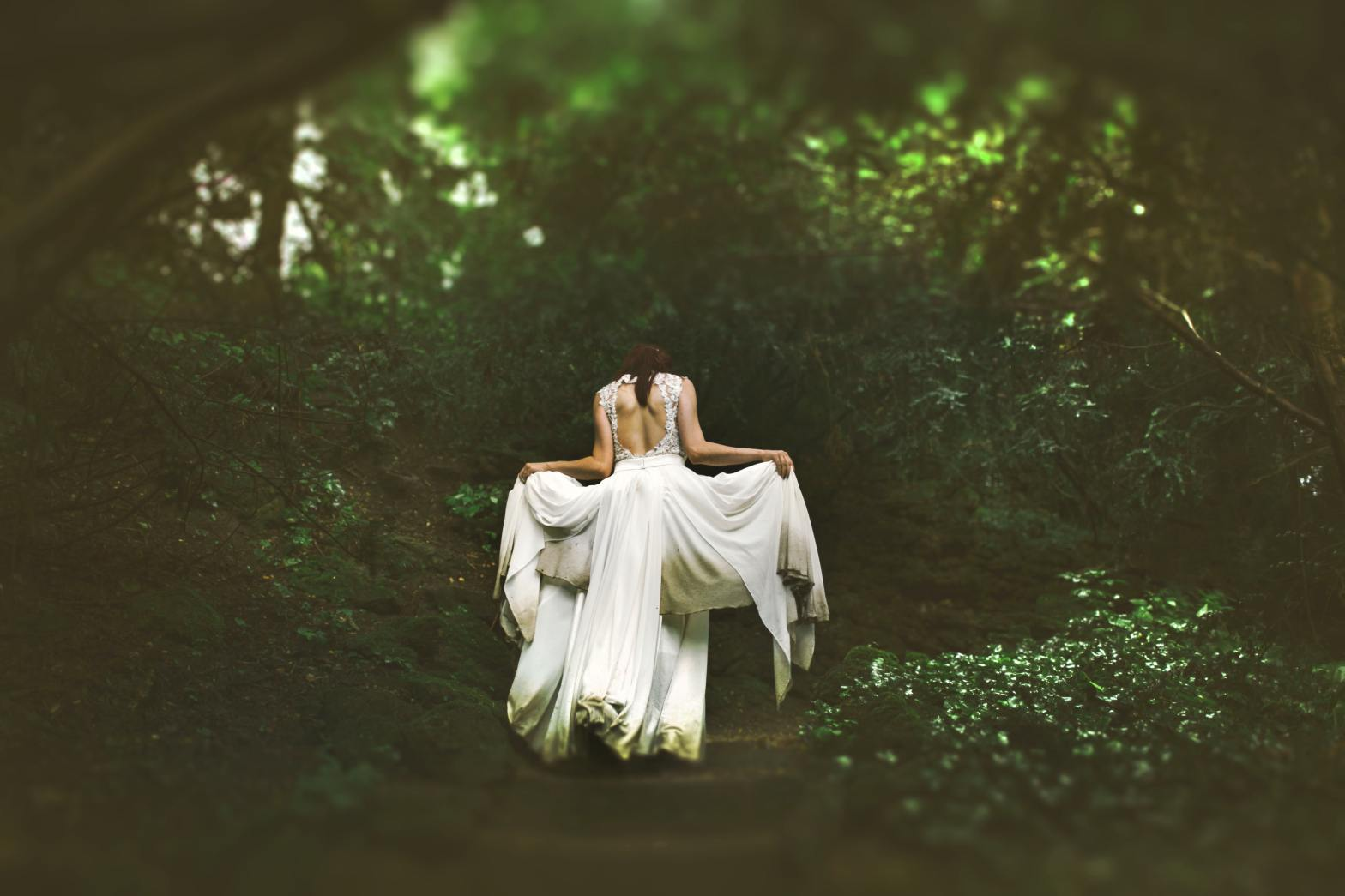 photo of woman in white dress in magical forest