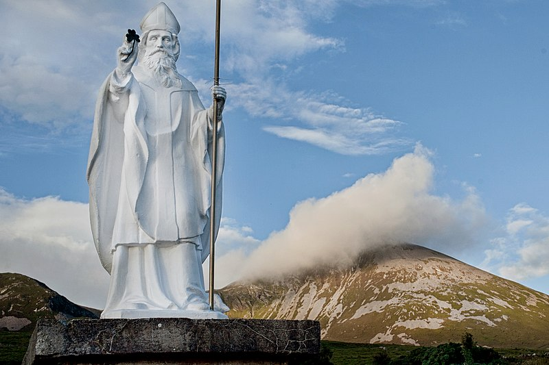 photo of a statue of St. Patrick at the foot of a mountain (Croagh Patrick)