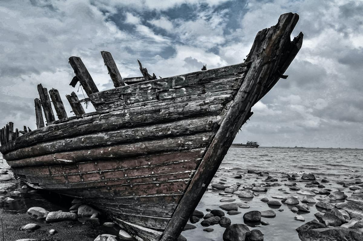 photo of derelict wooden ship on shore