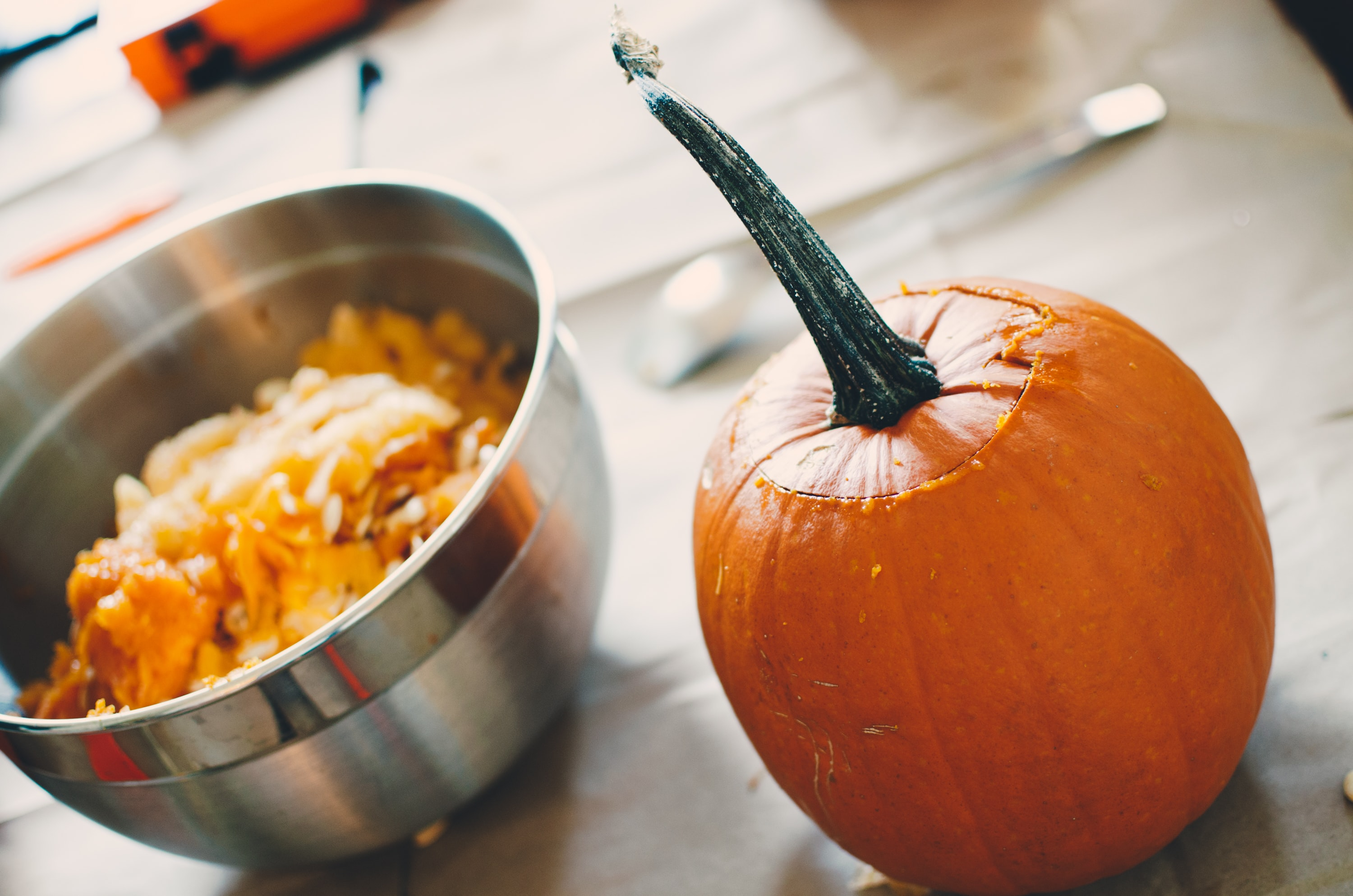 photo of hollowed-out pumpkin next to bowl of seeds and pumpkin guts