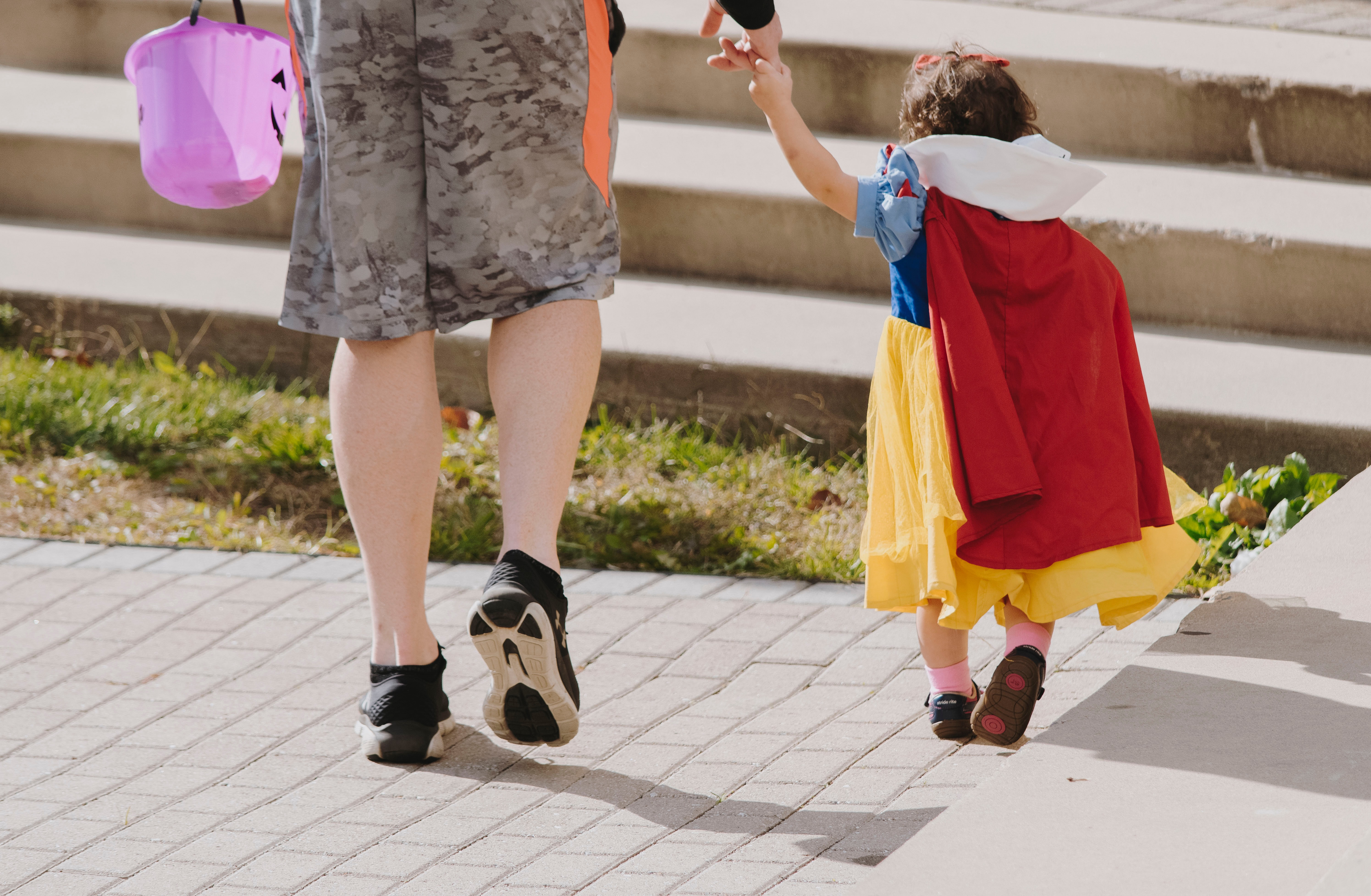 photo of parent taking toddler, dressed as snow white, trick-or-treating
